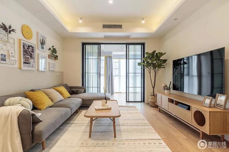 客厅浅灰色的布艺沙发搭配原木风的家具,营造和暖的氛围;沙发背景墙处摆放了几幅装饰画和绿植,空间不算很大,却点缀出文艺气息。