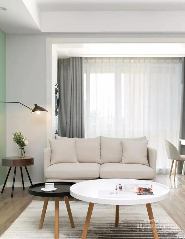 客厅地面通铺原木色地板,顶面采用点光源取代主灯,纳入阳台,拉伸空间视觉