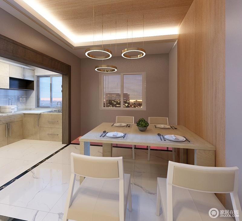 餐厅与厨房通过自有的墙体结构来分区,减去了门体后,让两个空间更有互动性;原木橱柜的空间朴素而实用,而餐厅区矩形吊顶内的嵌入式灯光搭配盘形吊灯给予空间简单时尚;驼色的墙面搭配板材的立面,中和出空间的温和,让主人可以落座于此,安心用餐。