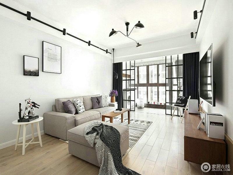 进门第一眼就是这个让人感觉很干净的客厅,在软装搭配上选用灰色布衣沙发、木色的家具、浅色的地板来营造空间的温馨感,深色的窗帘和黑色的灯具元素丰富了空间的层次感。