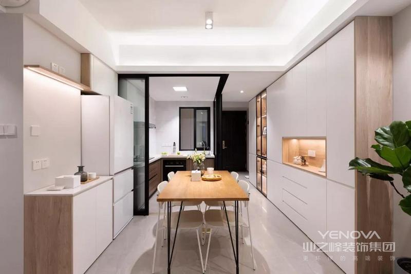 餐厨合一的空间,餐厅侧方的餐边柜一直延伸到了玄关处,另一侧也做了矮柜的设计,冰箱放在角落里,整个空间看起来宽敞又明亮