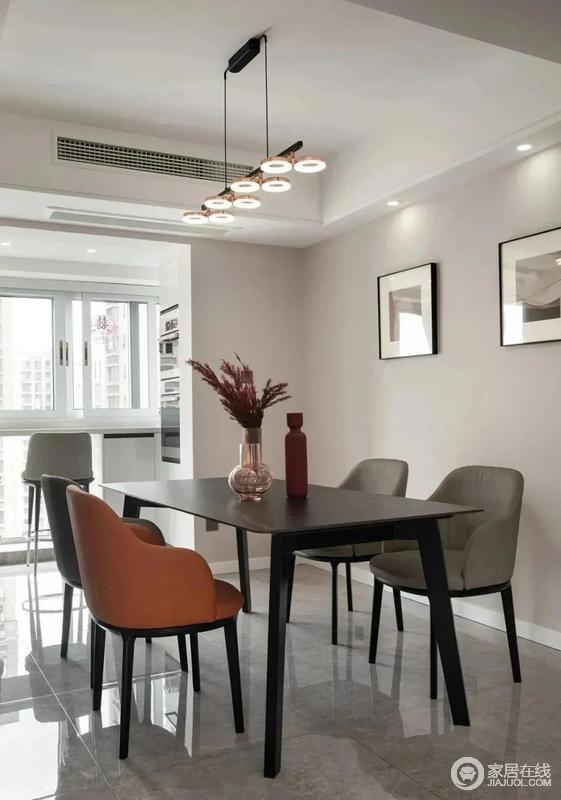餐厅简约浅薄的餐桌搭配现代简约的餐椅,黑灰色的基调中搭配橘色作为点缀,与玫瑰金的轻奢吊灯、挂画将气氛烘托得颇为温馨大气。