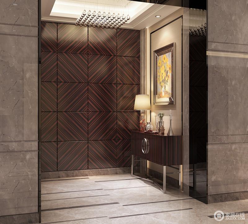 玄关与整体设计相匹配,延展着现代风的沉寂和冷冽;利用黑褐色实木板拼接成菱形的立面令空间多了几何立体感;小边柜质感上乘与玻璃流苏吊灯的柔和剔透呼应着现代质感。