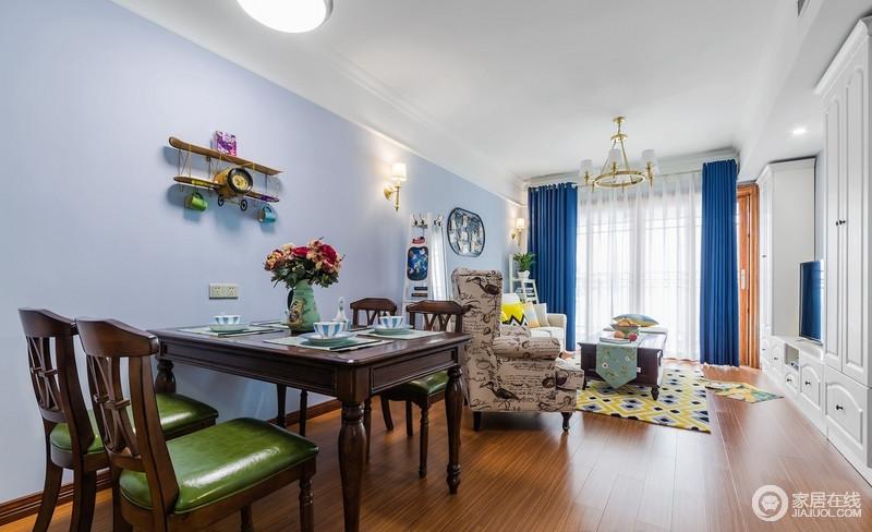 单人椅的色彩很好的衔接了餐厅和客厅,餐桌上的餐具很精致,餐具的颜色也是根据整体淡蓝色的空间而搭配,力求做到和谐,而美式实木家具赋予空间厚重感。