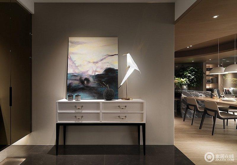 玄关地板以清洁方便的抛光石英砖铺设,与客餐厅区域做出分野,左侧墙面规划悬空置顶的隐藏式鞋柜,茶镜门面加深空间开阔立体的视觉感,下方设计间接照明塑造层次感。