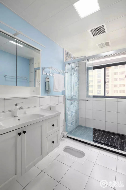 卫生间洗漱区的白色地砖延续到了腰线高处,配合天蓝色的墙面,营造格外清新的氛围。而淋浴间则以墙面花砖和地面黑砖加以区分。