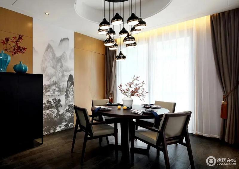 餐厅的地面铺贴了深灰色地板,圆形的吊顶内布置一组多灯头的精致吊灯,中式风的餐桌椅中正大气;木饰面中间加入一幅诗意的山水画墙布,使得用餐空间也更加儒雅而文墨舒适,可以说古韵犹存,满含东方心意。
