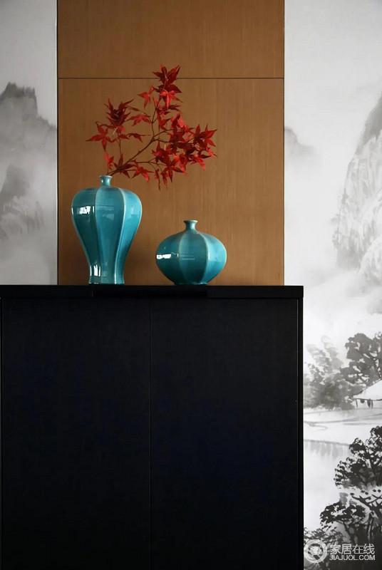 黑色的餐边柜布置在简约雅韵的十分的餐厅内,餐边柜上还摆了蓝色的花瓶,插上红色的插花,让空间更加具有中式的古韵气息。