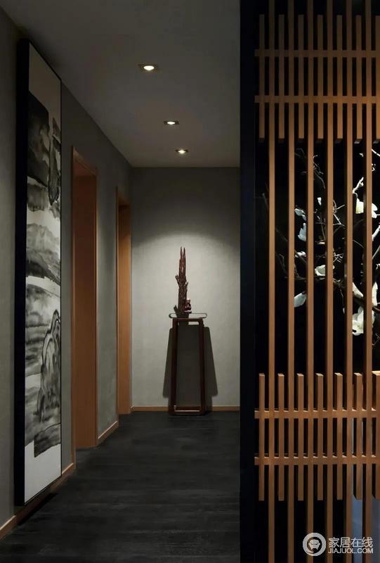 走廊在深色地面的空间基础,墙面刷成水泥灰的颜色,侧边挂一幅装饰墨色画,走廊尽头还有一个木质端景架,在筒灯的照射呼应下,带来一种成熟安静的视觉感。