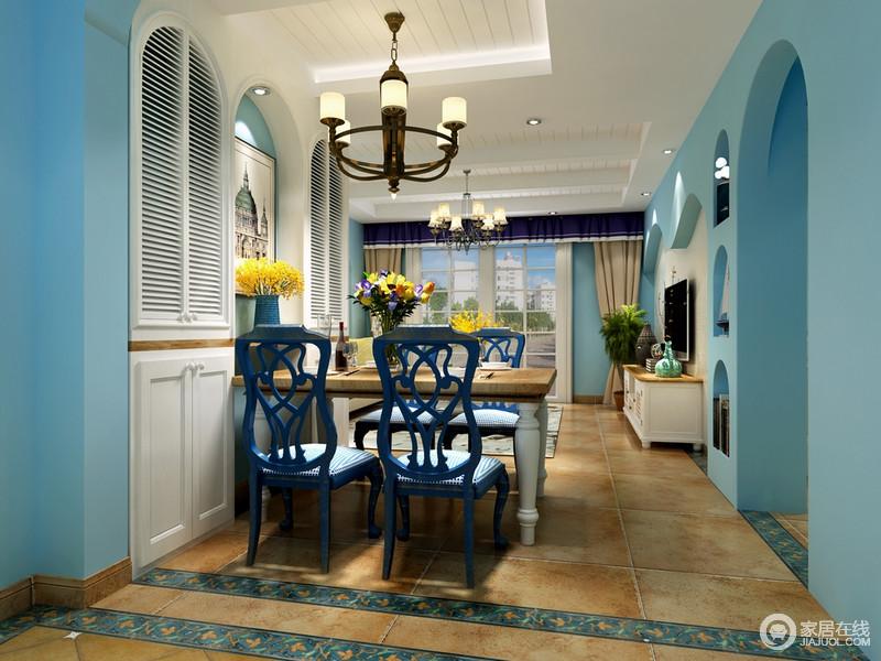 餐厅以米色砖石奠定自然与温沉,蓝色花砖框边与墙面涂刷的蓝色漆形成呼应,变奏出地中海的清湛;墙面拱形收纳柜的白色门简单和灵动之中,将造型艺术成就空间的圆润和饱满;铁艺吊灯的古旧和斑驳感与实木桌、深蓝色木椅形成别致,给生活带来不少的跳动。