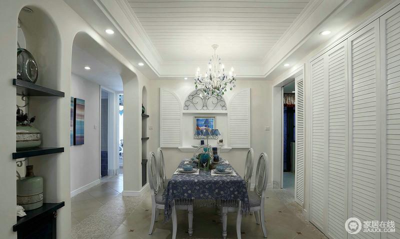 餐厅设微拱形的墙体与墙体的白色拱形门窗构成一种结构上的应和,让地中海风味浓厚;白色吊顶与浅驼色墙面也不失利落,而碎花蓝色桌布与木椅的精致,点缀着石墙内的置物架多了地中海的自在,而百叶柜门解决了嵌入式储物间对美观上的需要,简单中更显得体。