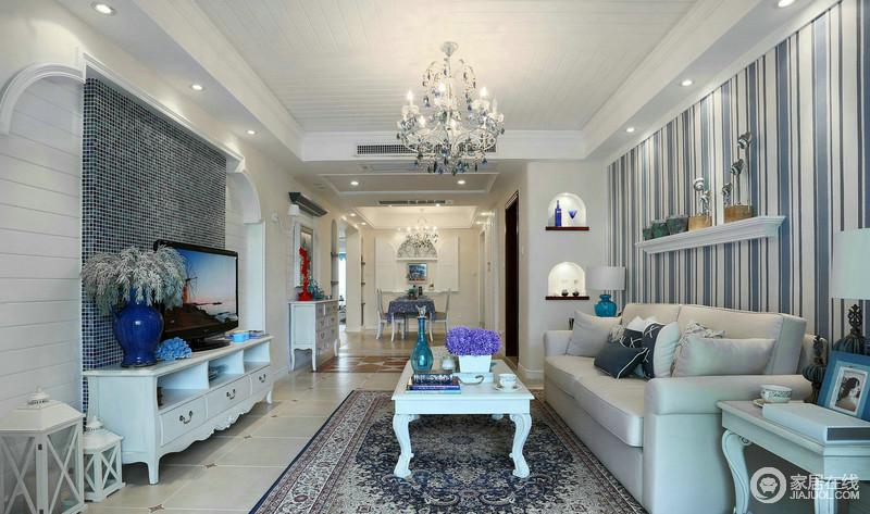 客厅也是白色主色调的设计,白色高质量的腻子粉,与板材打造得吊顶,让整个空间更为白净;蓝白条纹壁纸与布艺柔软舒适的沙发增加了贵气,而客厅地毯设计和茶几,枝形大吊灯吊在空中,以光增添温馨。