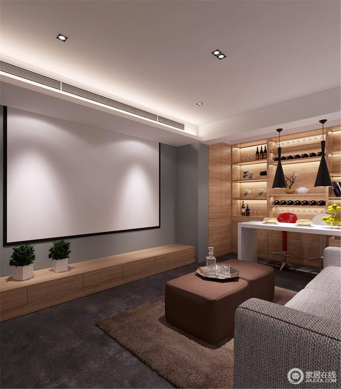 影音室在原本灰色立面的基础上,专门定制了一个原木酒柜,让生活更有趣味;吧台处的吊灯带着工业艺术质感与柜内的灯带打造着温馨,灰色布艺沙发与赤色坐凳、地毯在素静中,增添了一抹大地之色,格外自然。