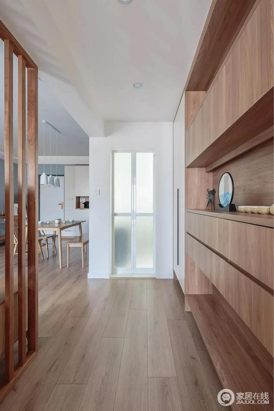走廊以原木质感的收纳柜实现功能性需求,与地板保持色彩上的和谐一致,又凸显质感;开放式的设计令空间通透不少,居住在这里也会舒适不少。