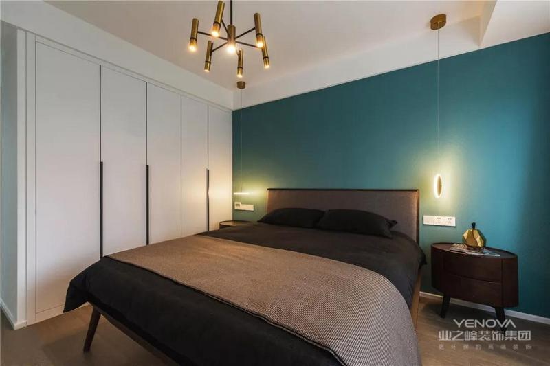 主卧以蓝色背景墙搭配深色卧床,营造出温馨静谧的空间氛围,有利于睡眠。古铜色的吊灯,兼具美观性与实用性。床头两盏吊灯散发出柔和的灯光。