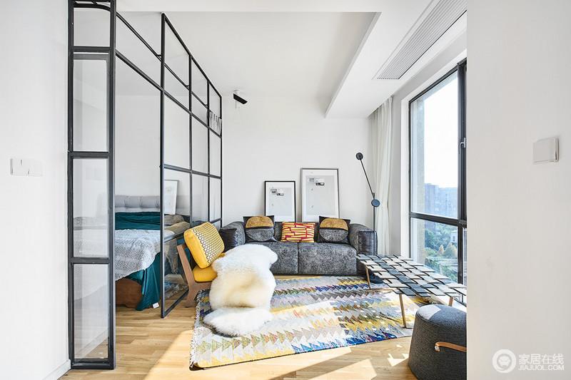 客厅与卧室以玻璃格栅分隔空间,看似小巧却不失生活的温馨;灰色沙发因为彩色地毯不显得沉闷,家具配饰组合,带来一种色彩的明快。