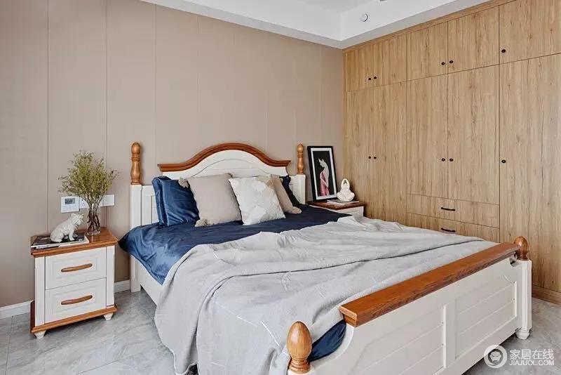 卧室床头墙以胭脂米色的软包背景,搭配木白结合的美式床与床头柜,营造一股淡淡的温馨;定制的一个木色现代衣柜极为实用,而蓝色和灰色床品组合,朴素简单,也十分舒适。