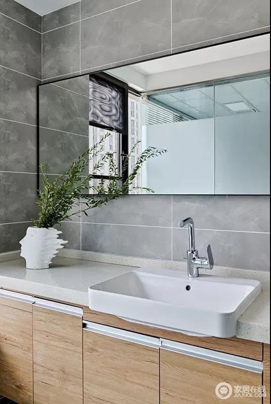 卫生间木色洗手柜,搭配嵌入式的台上盆,简约实用,人像花瓶更是雕刻着艺术时光;灰色的墙面砖与镜面收纳柜以明暗的方式表达材质艺术,营造出一个自然利落的空间。