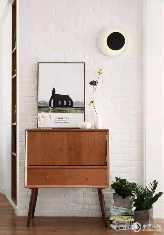 入户门厅处做了一个文化砖的背景墙,搭配一个深木色的端景台和独特的壁灯、装饰画等,构造出一个简洁而又有创意的北欧风空间。