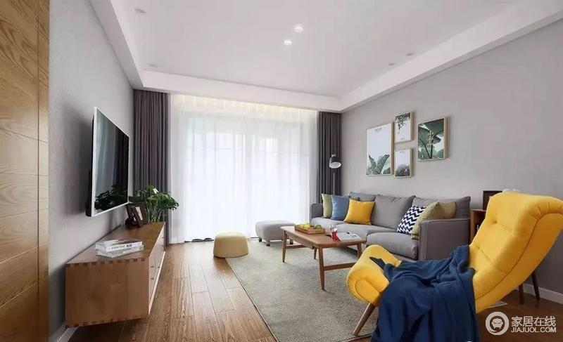 在玄关门厅的侧方就是客厅空间,两侧墙面都刷成了灰色系,搭配木质电视柜、茶几和绿植、单椅等作为点缀,增添客厅的自然感、舒适度。