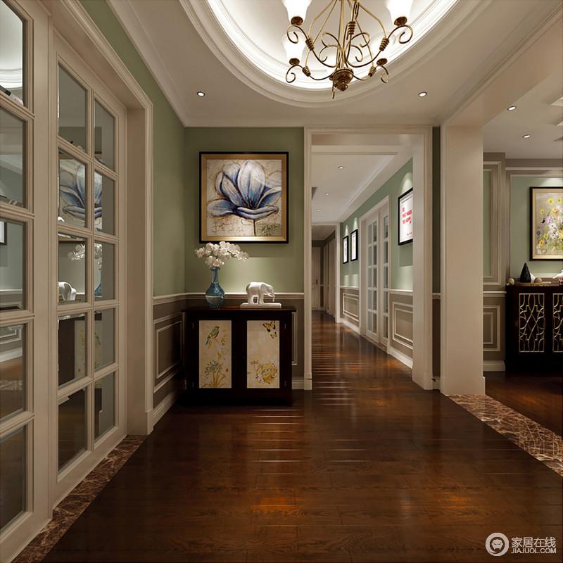 门厅因为石膏造型和挂画的装饰显得十分庄重和利落,绿白相间的设计,更显清和;走廊的一角放置了中式风的实木边柜并搭配艺术画、花器和饰品,营造简明却讲究的生活氛围,带给生活无限的轻松和美感。