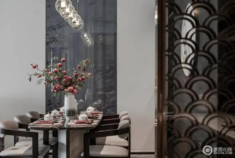 餐桌连贯着客厅空间,餐厅背景墙一幅圆形的挂画,与餐桌上方一排气球状的玻璃灯泡形成呼应,也使得用餐空间更加温情华丽而高级精致;石材餐桌+实木架的布艺餐椅搭配得十分和谐,桌上也摆设了中式风的餐具,再加上一束红色花卉与桌巾呼应, 营造了一种温馨与喜庆。