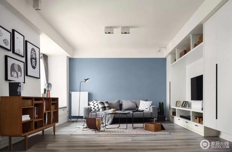 因为空间已经存在大量的浅色,灰中式含蓝的深色沙发墙使整个空间尽显优雅,搭配实木的家具的质感协调出生活的稳重雅致;壁柜式的电视柜内置储物区,对面就是飘窗,可以享受阳台洋溢;实木橱柜搭配时尚的茶几、落地灯,营造出一种放松和惬意的氛围。