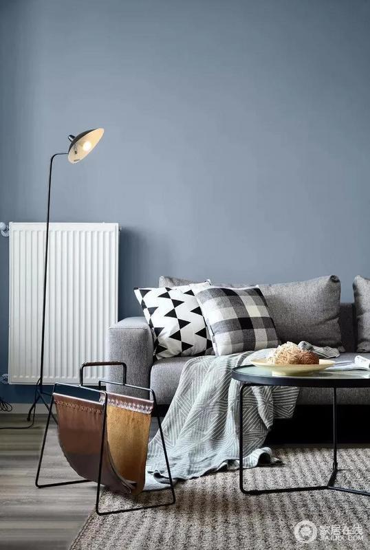 灰色的布艺沙发十分耐看,两只黑白图案各异的抱枕凸显着一种生活美学,正好与灰蓝色的墙面组合出忧郁之美;小巧的皮革书架、驼灰色的地毯带你品味北欧的朴质,却生活出一种独特的精致感。