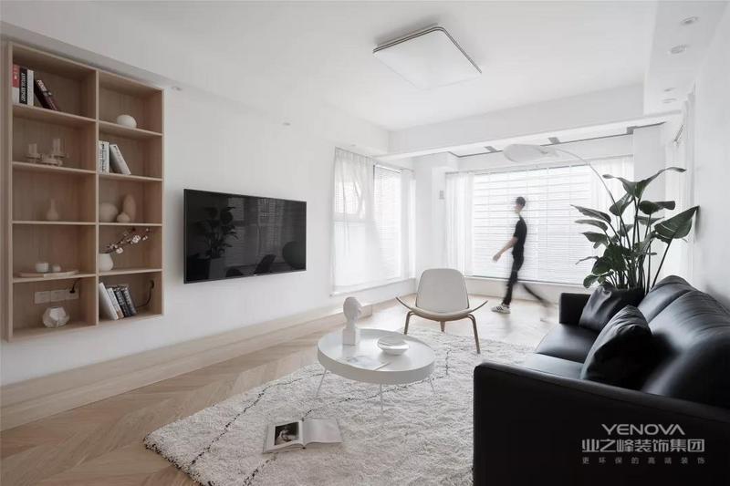 ▲现代简洁的客厅,电视墙取消了电视柜,在壁挂电视机左侧装了一个木质的展示架,布置上书籍与陶艺品,让空间显得自然而气质。