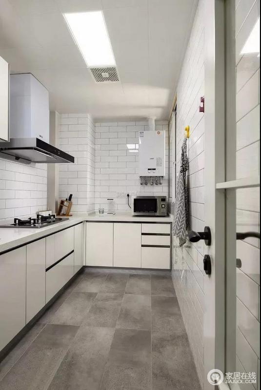 厨房L型的格局因米白色橱柜与黑色边框强化出结构和造型美学,同时,白色小方砖、深灰色地砖形成一种强烈的反差,材质组合之间以层次成就空间的实用与美学。