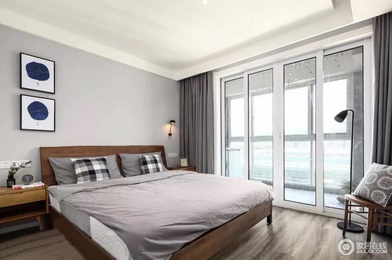 卧室的落地窗自造空间的明快,深灰色窗帘与墙面的浅灰色形成层次感;实木家具搭配黑白灰格纹床品,与简易的装饰画、精致的壁灯,使整个卧室空间安详静谧。