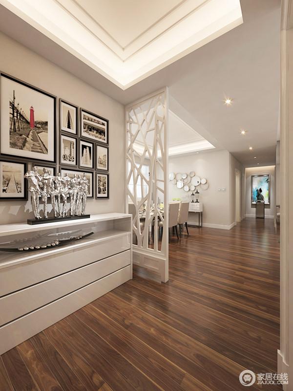 门厅通过白色实木隔断作简单的空间区分,却不失空间之间的互动性;褐色的地面赋予空间沉稳,而白色玄关柜搭配黑白色的挂画组合,让空间具有文艺气息,也足够实用和大气。