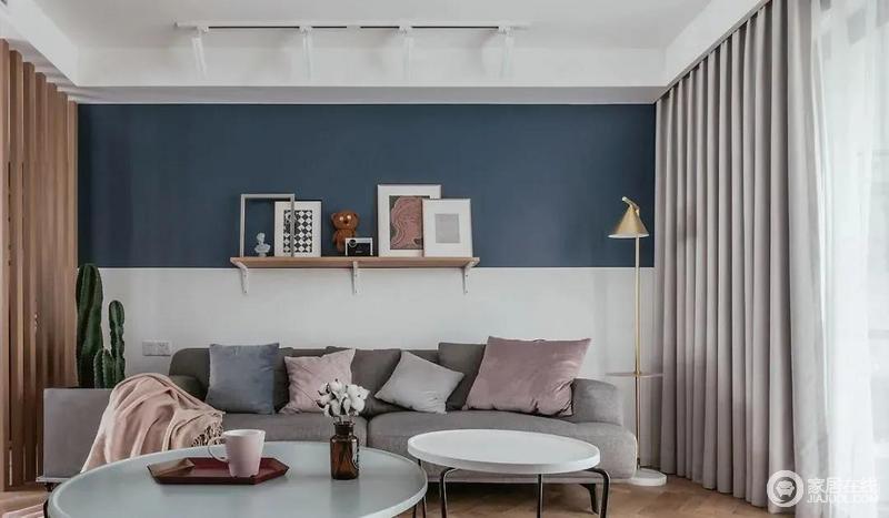 客厅沙发背后的拼色墙面化解了空间的单调,搭配收纳木架,营造一份简单之美;黄铜金属落地灯十分小巧,与圆形茶几搭配,强调空间美学。