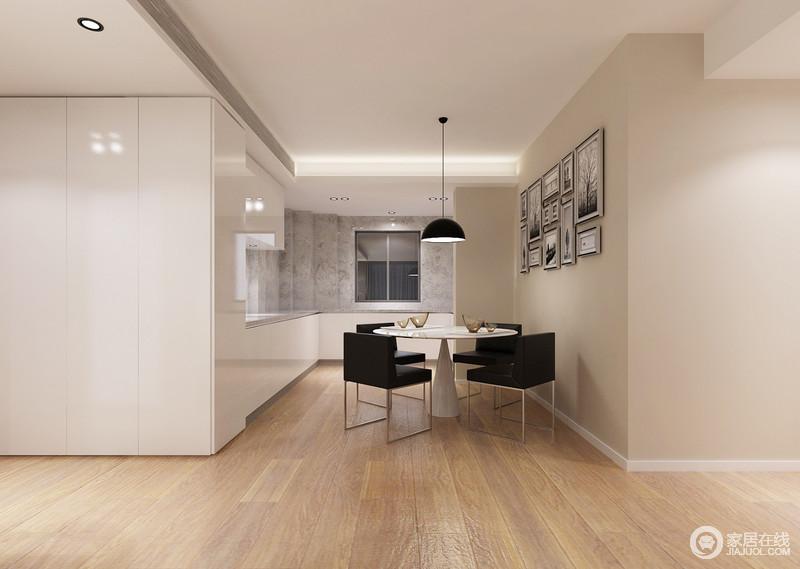餐厅以白色烤漆板打造厨柜,因为灯光交错,让空间多了份光亮;原木地板与驼色漆的墙面给空间带来恬淡,黑白挂画、吊灯与黑白组合的餐桌餐椅装饰生活的简单与时尚。