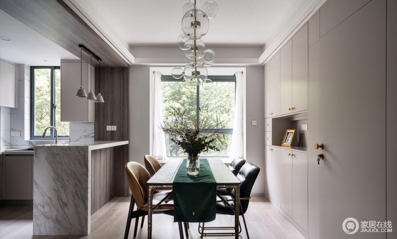 餐边柜做了整墙的收纳空间,中空预留位置,在厨房台面不够用的情况下,现代时尚地餐桌椅组合出都市之风,绿色的桌旗搭配绿植,带来自然清新,而玻璃吊灯的通透与吧台的北欧灯组合,让空间颜值翻倍。