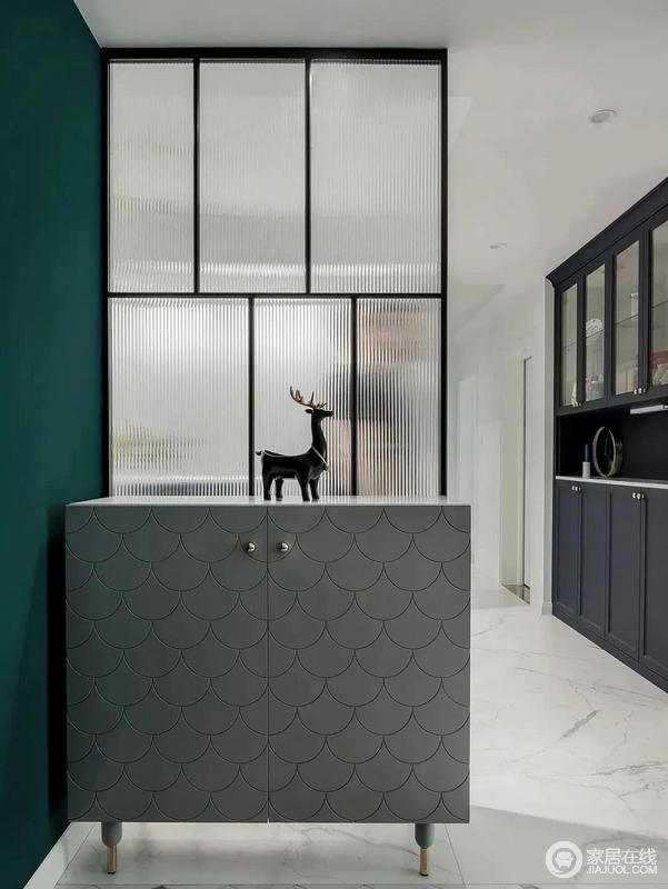 门厅原本的墙体被敲掉,以玻璃做隔断,搭配鱼鳞纹灰色鞋柜,增加了空间的时尚感,同时也解决了原本入户采光不足的问题,令空间更为精致。