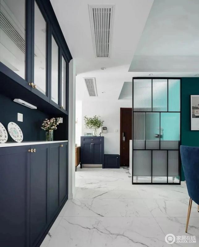 进门的右侧放一组臧蓝色玄关柜和脚凳与灰白天然纹地砖在色彩反差之中,营造蓝白雅静,绿植点缀其间,多了一份自然的清爽。