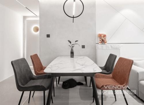 餐厅的立面与客厅部分以不同材质打造,有一个区域性的划分设计,让空间各有特色;由于考虑到层高及后期能耗的问题,业主选用了暖气片,即开即热相对还是比较方便,大理石立面的餐桌搭配黑灰色和砖色的餐椅,让空间更显简约之美。