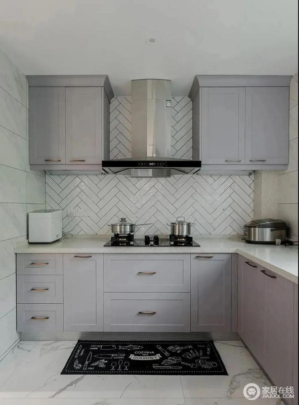 厨房的立面铺成人字拼的小白砖,与墙面的米色砖石以强烈的反差构筑几何美学;青灰色的橱柜少了暗沉,反而与整个空间十分契合,收纳之中构筑大气。