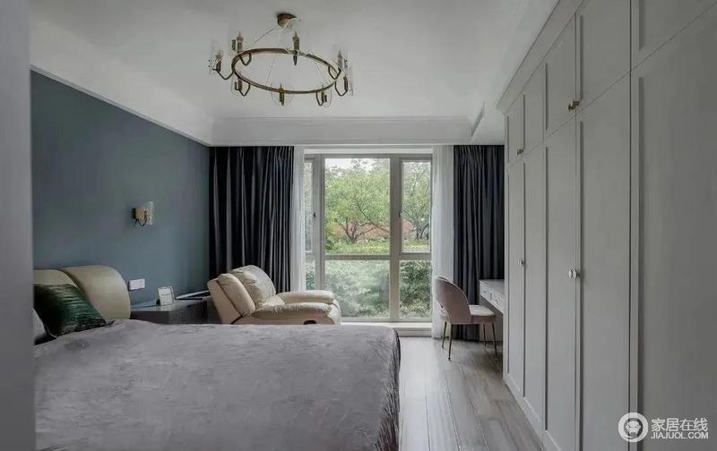 主卧选择暗蓝色为主题色,搭配浅灰色的衣柜,在冷色之中构建一个舒适的氛围;芝华士的休闲沙发与软软的大皮床搭配得十分融洽,再加上深灰色窗帘与白色纱幔镌刻着一份稳重,调和出温情。