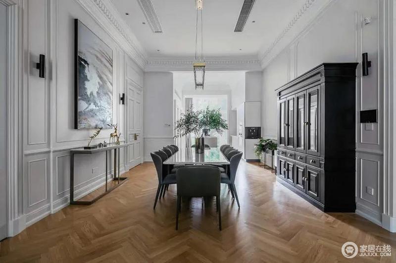餐厅在中间位置摆上多人位的长餐桌,两侧分别是端景台与收纳柜,在艺术与实用之间,布置出一个精致优雅的用餐空间。