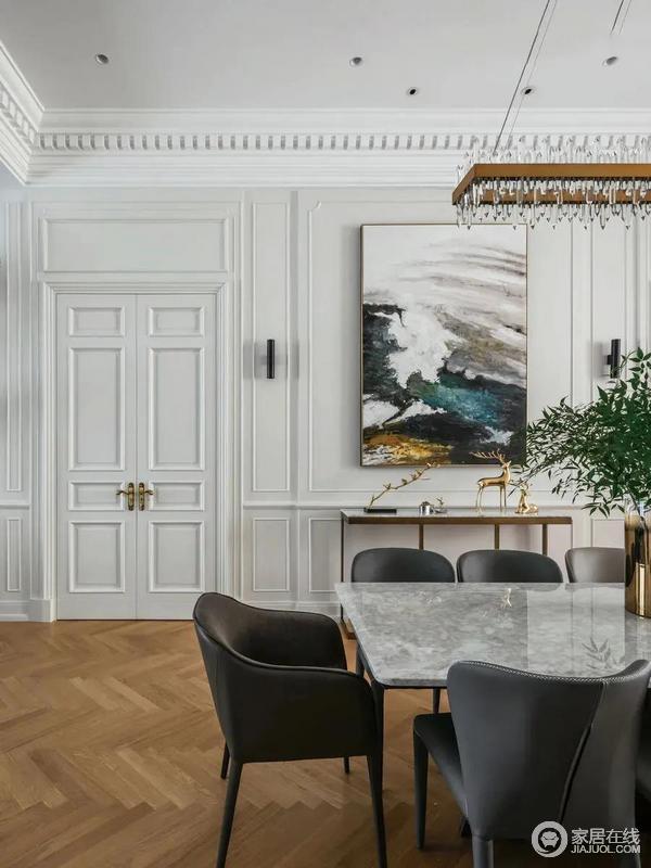 石材台面的餐桌,搭配灰色皮质的餐椅,上给餐桌上方的金属架+水景吊灯,也让用餐空间显得更加精致华丽而档次。