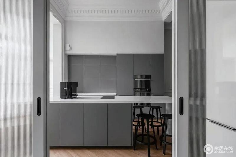 厨房区域以长虹玻璃推拉门隔了出来,里面西厨式的设计布置,在简约灰白配的色调设计下,营造出一种现代舒适而时尚的烹饪环境。
