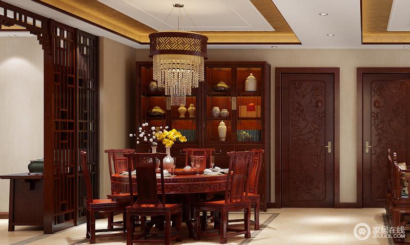 空间看似朴厚温然,实则处处透着细腻华贵;与吊灯上下呼应的圆桌,轮廓上刻画着优美雕花,搭配身姿挺拔的高靠背餐椅,在色泽莹润的红木凸显下,有着内敛低调的奢意;桌上瓶花点点渲染,释放自然芬芳烘托就餐气氛;功能酒柜则紧靠墙面,与房间门和谐配搭。