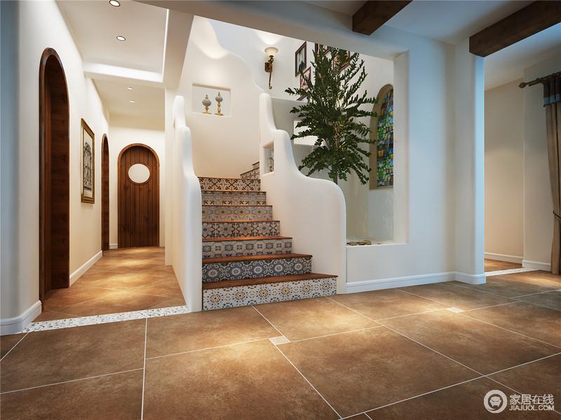 """门厅以拱形门搭配挂画的形式,让空间具有田园生活的惬意和随性,虽然地面都铺贴了褐黄色和深驼色地地砖,却以不同的形式,表现工艺的独到;通往二楼的楼梯采用""""s""""一样的曲线设计,并借灰色拼花砖来转变了刻板过于理性的几何造型,再加上扶手的独特设计,让空间具有浓郁的地中海风情。"""