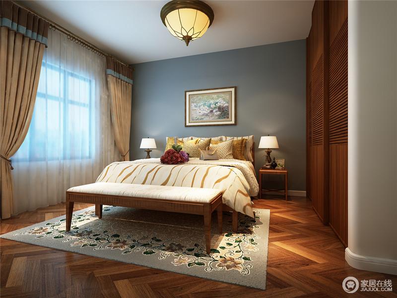 """卧室以藏蓝色漆为背景,在油画的点缀下,与地毯形成不一样的花卉艺术;房顶装饰性的""""假梁""""和""""洞门"""" 最大限度的保留了原始的色彩和质感,与木衣柜和菱形地板呈现出淳朴且丰富独特的艺术效果,对称的床头柜搭配床尾凳,提升了生活的温馨与质感。"""