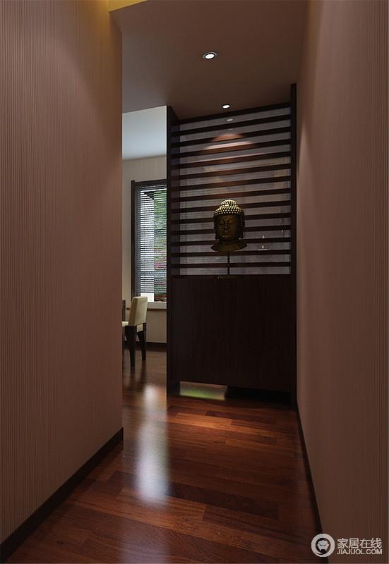 走向餐厅的走廊设计得十分简洁,壁纸和原木地板装饰出了温实与朴质,定制得隔断上挂置了如来佛头像,让生活多了份禅静和庄严。