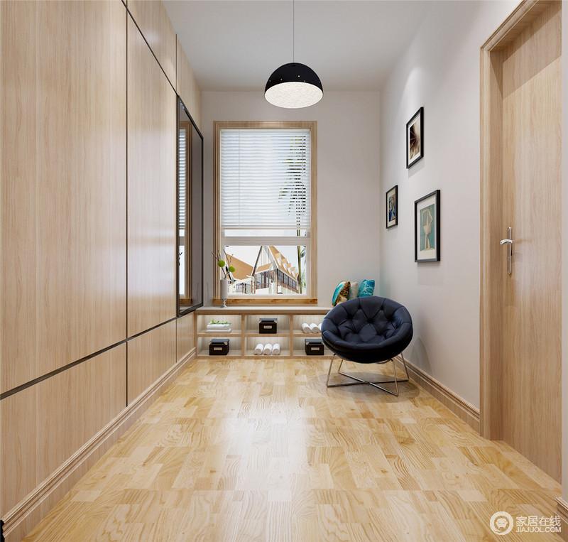 门厅的空间专门定制了一个储物柜,既解决了墙面收纳的问题,同时,搭配整体空间的原木设计,十分朴质;挂画、吊灯抑或地柜和单椅,都构成生活的隽意场景,让你回到家便是一阵温馨。