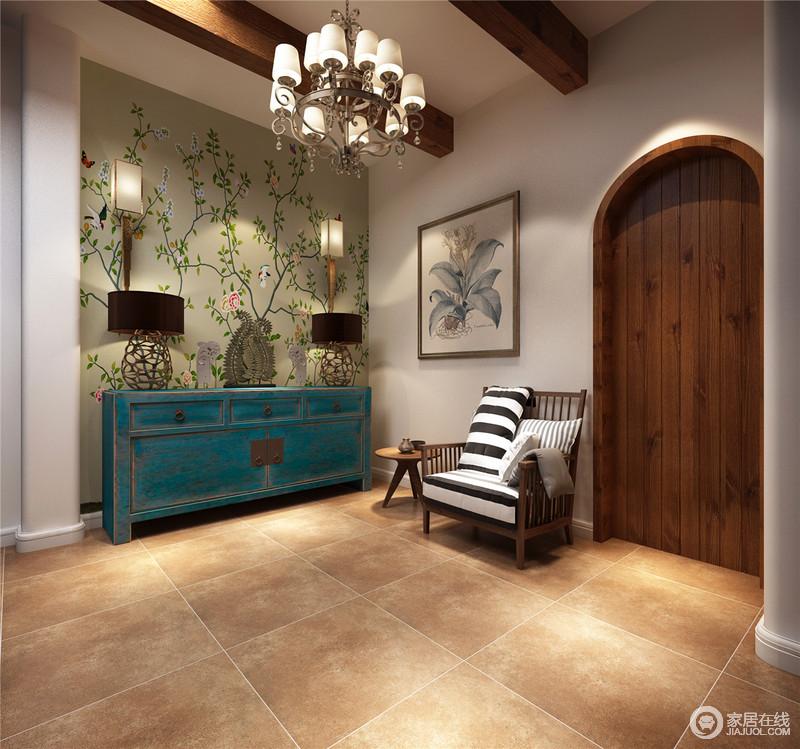 门厅的设计看似因为拱形木门、绿色花卉背景墙、挂画显得自然清新,却因为蓝色古董木柜、金属底座地台灯、黄铜吊灯塑造了现代时尚和轻奢;老式的柜体磨损的老旧感与木椅上黑白条纹靠垫搭配在一起,重新让空间生动而有趣。