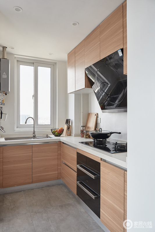 开放式设计让厨房不再是一个单独个体的空间,空间上既避开了与其他区域的相互交叉影响,又具有自己的功能性;木色橱柜与白色墙面,干净中凸显出一种淡暖的格调。